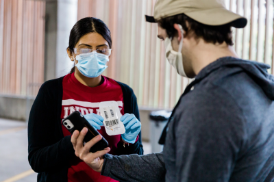 a worker shows a student how mitigation testing works
