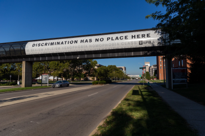 An anti-discrimination banner hangs from the Michigan and Blake streets walkway