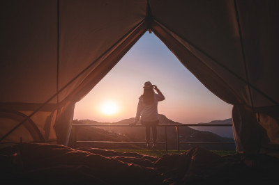 Woman looking at sunset in tent