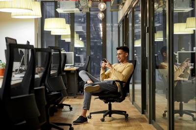 A man reading his phone at work