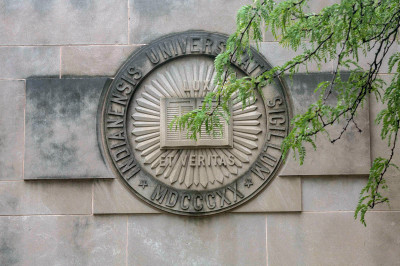 IU seal in limestone on the side of a building