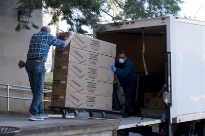 Two men unload boxes of digital keyboards from a truck