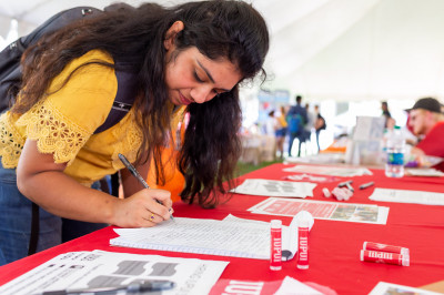 A student signs up for an event in the WOW Involvement Fair on the IUPUI campus