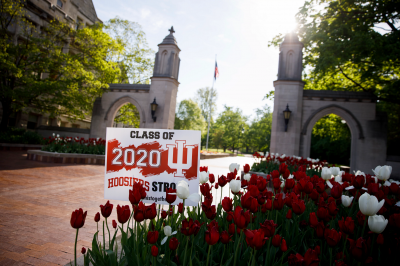 """A Class of 2020 sign saying """"Hoosier Strong"""" is next to tulips in front of the Sample Gates."""