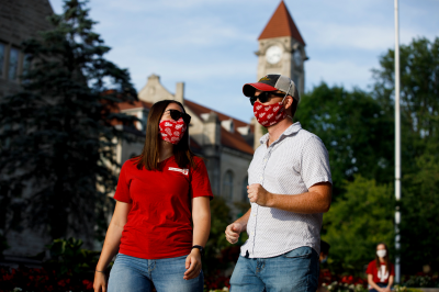A couple wearing IU face masks walks on the Bloomington campus