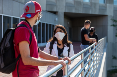 Students talk on the IUPUI campus while wearing face coverings.