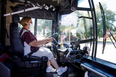Masked bus driver sits behind glass barrier