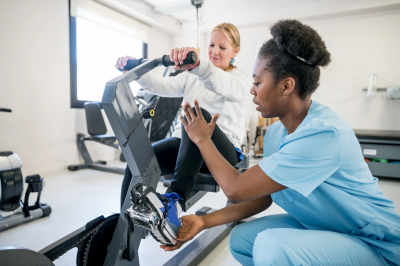 a woman in scrubs helps another woman with physical therapy
