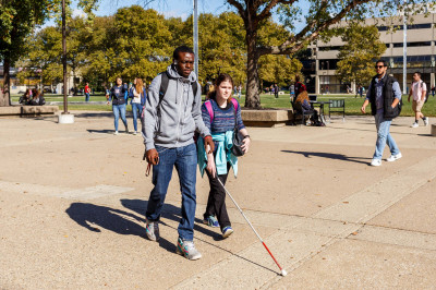 A student walks alongside a student who is blind.