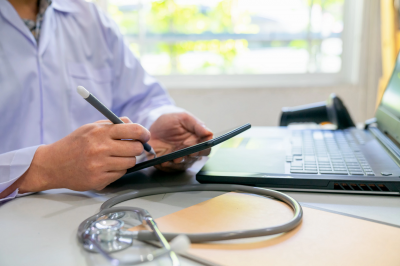 a person's hands with a tablet and stethoscope
