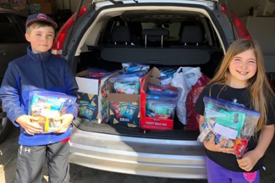 kids stand outside the trunk of car filled with goodie bags