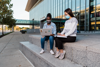 Two students sitting outside wearing masks at the Campus Center