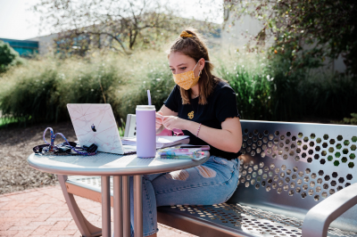 Student studying outside University Library at IUPUI.