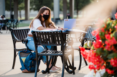 a woman sits at table outdoors on her laptop