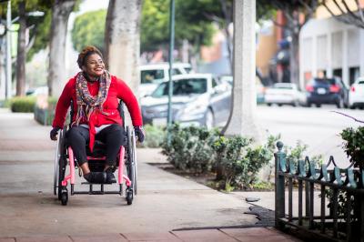 A woman uses a wheelchair on a city sidewalk