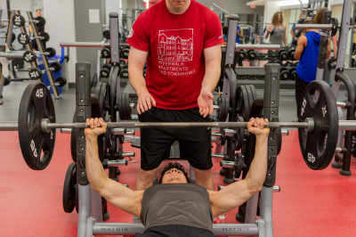 Two students use the bench press, one lifting and one spotting, in Jaguar Campus Recreation.