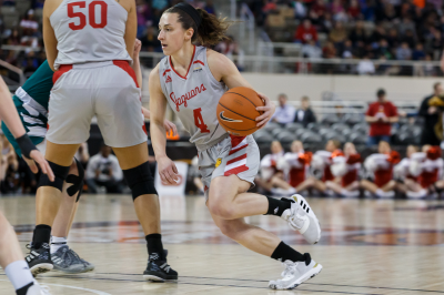 a woman basketball player drives into the lane during a game