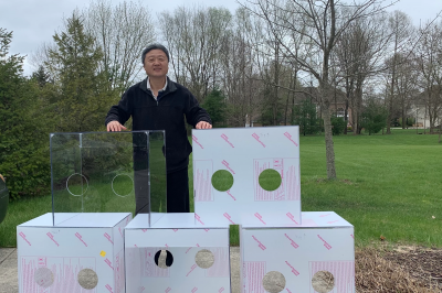 a man stands with intubator boxes he built