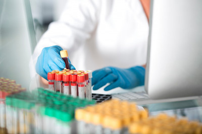 Close-up of lab technician examining test tubes with liquid in laboratory