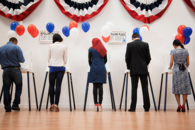 people standing at voting booths