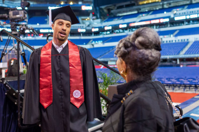 George Hill stands in a cap and gown before giving a commencement speech