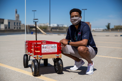 A student kneels down next to a red Riley wagon