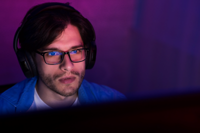 Man wearing glasses looks at a computer screen