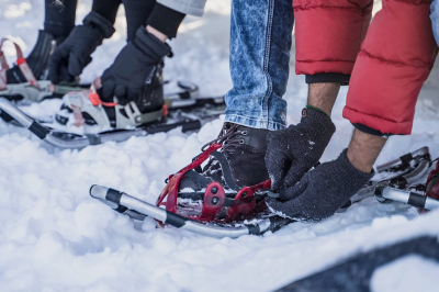 a person secures a snowshoe