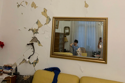 a boy looks into a mirror on a wall cracked with damage from an earthquake