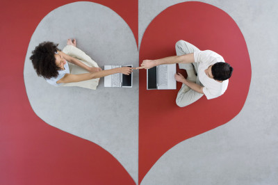 A couple sitting in different parts of a heart on the ground