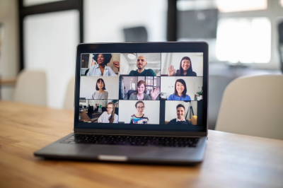 laptop screen shows people holding a virtual meeting