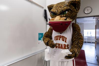 an IUPUI mascot cleans a classroom