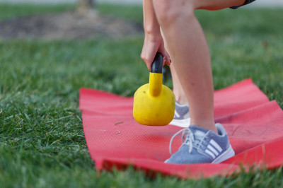 a person kneels with a kettlebell in their hands
