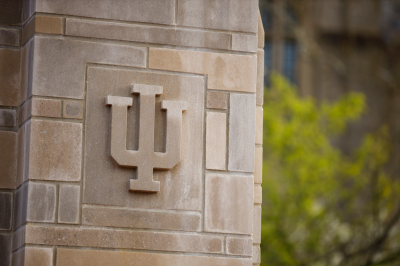 The IU trident is pictured in stone on the side of a building.