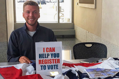 A student sits ready to help other students register to vote