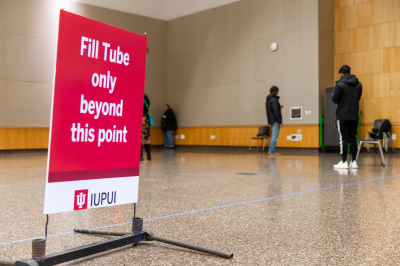 """a sign that says """"fill tube only beyond this point"""" with people in the background"""