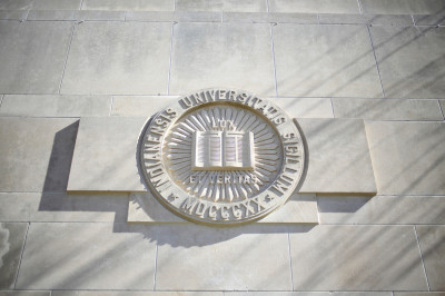 The Indiana University seal engraved on a limestone building.