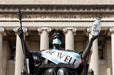 A statue by Columbia University Library wears a mask and a sign that says 'be well'