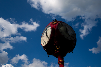 red campus clock set against a blue sky and white clouds