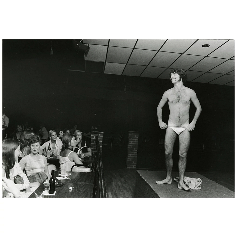A man stands on stage in undergarments