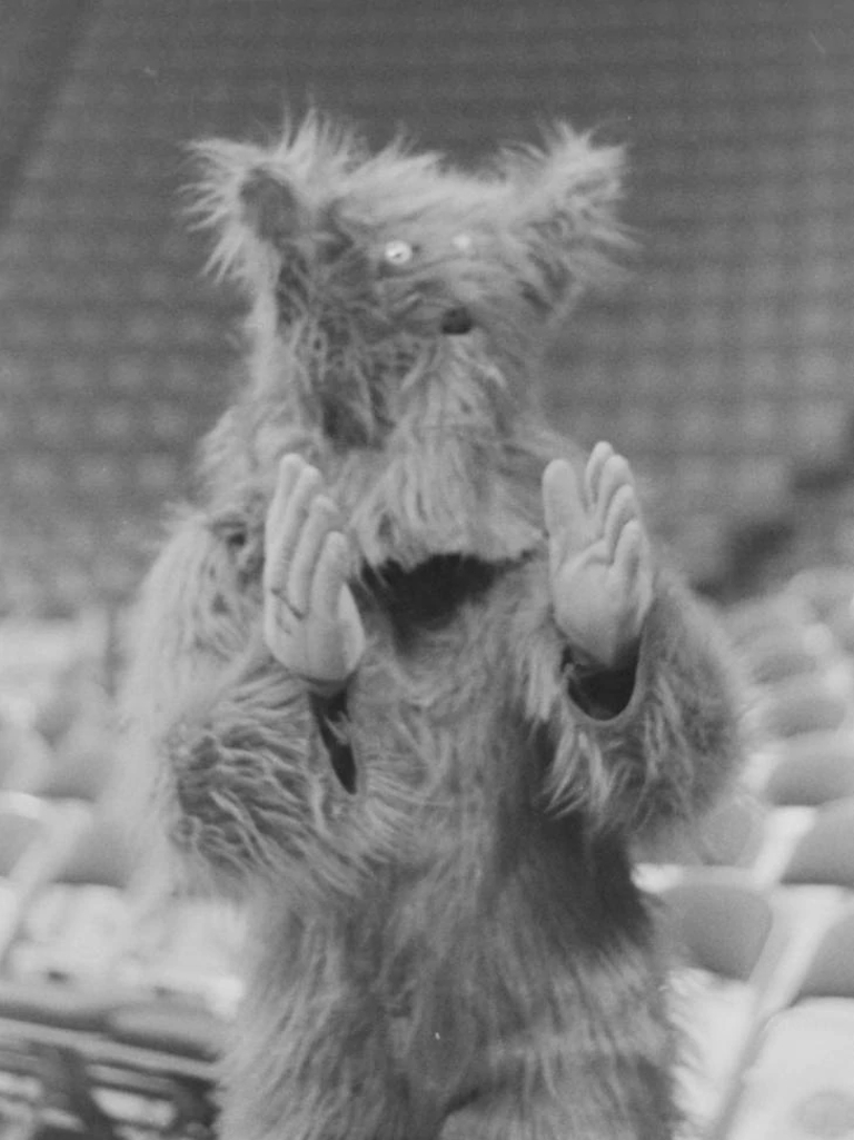 a furry, hairy and rather scary mascot creature claps its hands from 1979