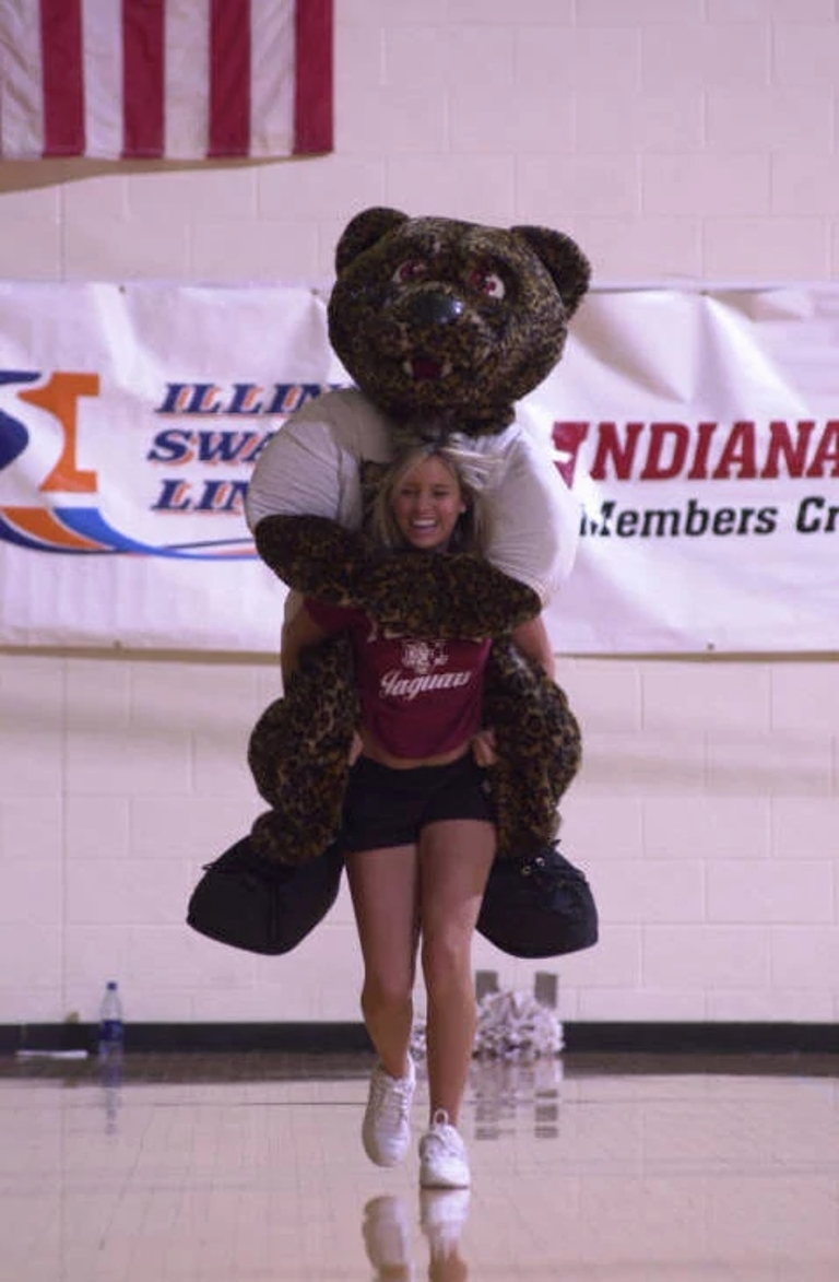 a cheerleader carries jinx the mascot on her back