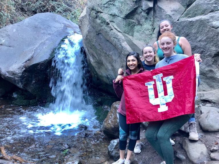 Students pose with an IU flag
