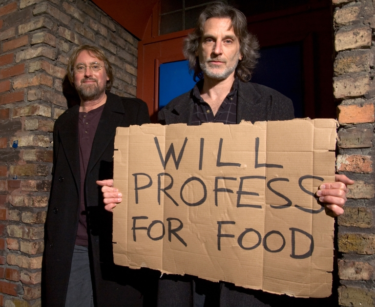 "Andy Hollinden holds a sign that reads ""Will profess for food"" while standing next to Glenn Gass"