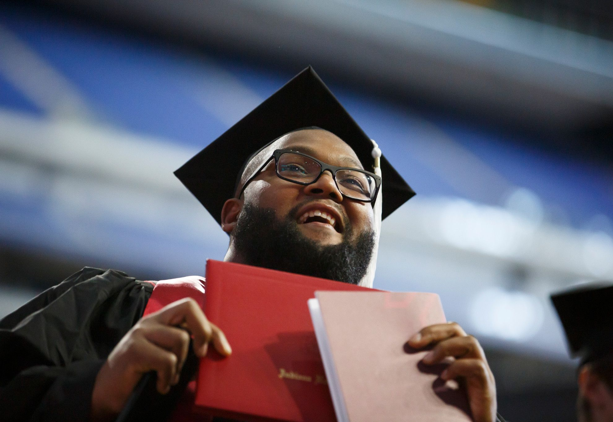 A man holding a diploma, wearing a cap and gown