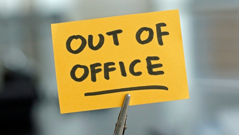 "a sticky note with ""out of office"" written on it"