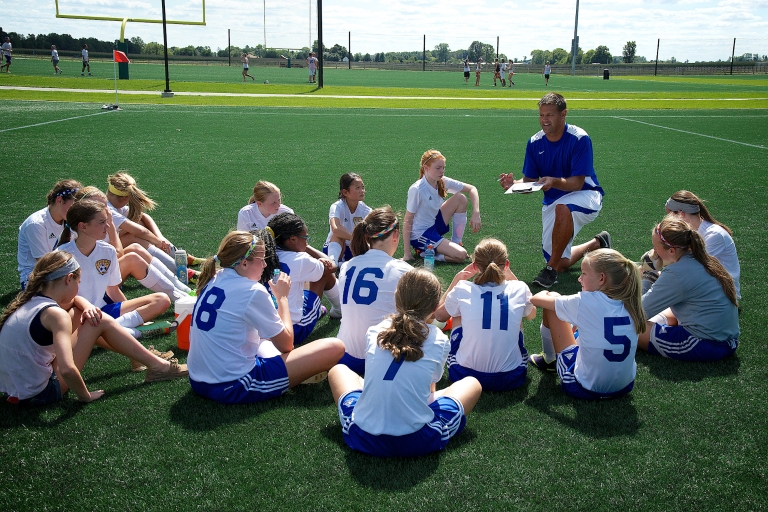 youth soccer players gather around their coach