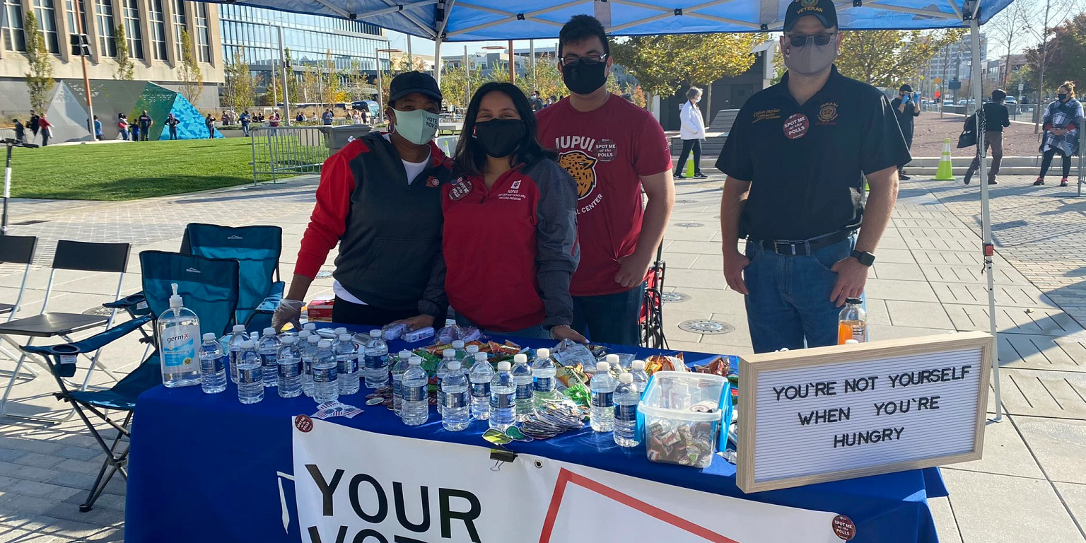 Volunteers stand under tent with food and water while wearing masks