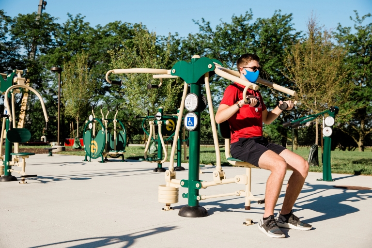 A person wearing a mask uses fitness equipment outdoors.