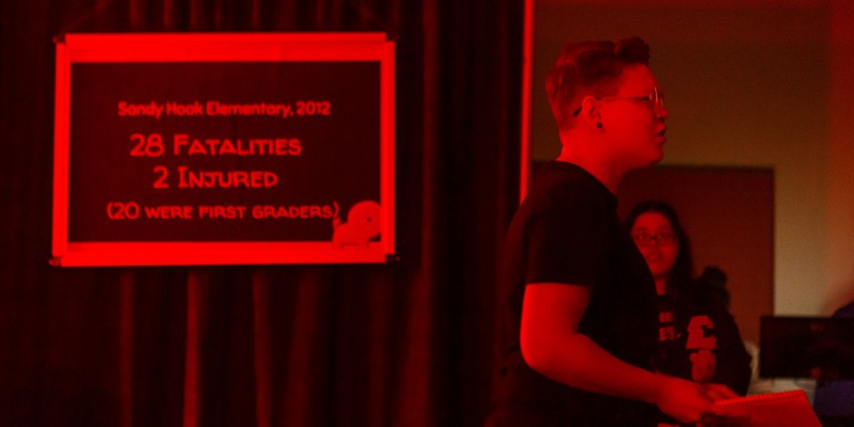 A student acts out a scene, shot in red lighting, about school shootings.